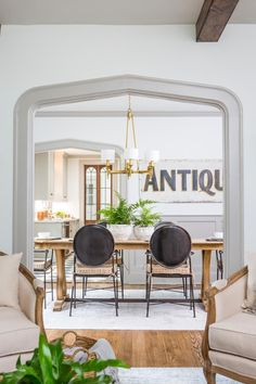 Joanna Gaines Style 80220437097117364 - A gorgeous gothic arch in a 1927 Tudor renovated by Fixer Upper's Joanna and Chip Gaines. This classic yet modern dining room features black dining chairs, a huge ANTIQUES sign, and a rustic farm table. Fixer Upper Hgtv, Fixer Upper Decor, Fixer Upper House, Dining Room Table Decor, Dining Room Walls, Dining Room Design, Living Room, Fixer Upper Dekoration, Joanna Gaines