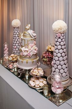 A stunning dessert table features two purple macaron pyramids topped with pomanders of cupcake liners.