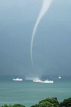 Waterspouts (at least, those classified as non-tornadic) generally begin their life cycle at the water's surface before climbing up into the sky. They occur in high humidity, when warm water temperatures interact with cold air.<3