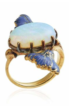 RENÉ LALIQUE - AN ART NOUVEAU OPAL AND ENAMEL RING, CIRCA 1900. Centring an oval cabochon opal between enamelled poppy flowers, opal later added, with French assay marks for gold, signed Lalique.