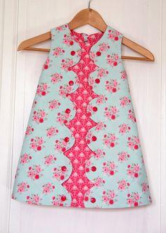 Vestido floreados en tonos rosas, en medio con adorno en otro tono rosa mas fuerte