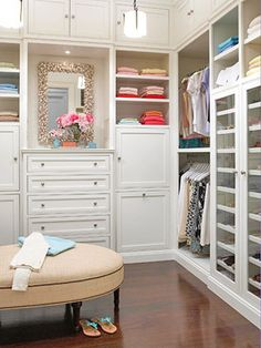 master bedroom closet, hers? white, built in chest, etc. need more rods, fewer drawers & shelves? pretty. wood floor, ottoman
