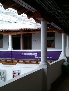 Los pasillos del segundo piso de un patio central con techos de teja.