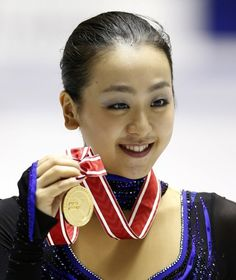 Mao Asada of Japan poses with her gold medal during an awarding ceremony at the NHK Trophy figure skating in Tokyo, Saturday, Nov. 9, 2013. ...