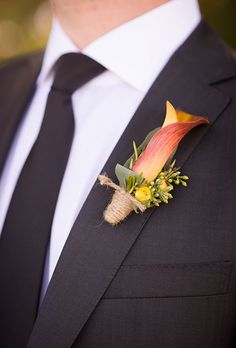 Brides.com: . A red-and-orange calla lily boutonniere, wrapped in twine and accented with greenery, created by Amy Burke Designs.