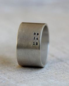 Men's personalized ring. Eco-friendly sterling silver custom band for men or great woman's band too . This wide band ring can be hand stamped with a personalized date, name or anything else you would like. The ring measures 11mm high. Because of the hight of the band I would suggest that you order 1/2 a size larger than your normal size. The text runs vertically along the ring in the photos but I can create the ring anyway that you like. When checking out please let me know what you wo..