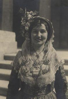 """Ασπρόμαυρη φωτογραφία γυναίκα με φορεσιά από την Κέρκυρα. Πίσω στάμπα: """"PAYSANTES DE CORFU"""", """"ΧΡ.ΠΕΡΟΥΛΗΣ ΚΕΡΚΥΡΑ 1951"""" και χειρόγραφα: """"Αγαπητέ Μπάμπη"""", """"Σου εύχομαι ευτυχισμένο το νέον έτος 1954"""", """"Σ.Αρβανιτάκη"""". Συλλογή Πελοποννησιακού Λαογραφικού Ιδρύματος"""