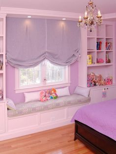 The built-in window seat and lilac fabric tie in with the walls. The lavender Roman shade is relaxing and creates balance and serenity while adding simplicity to this girl's bedroom.