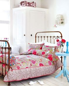 Cama de forja con colcha en tonos rosas