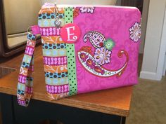 This little e-reader case was made for a sweet young lady to carry to school.  It has a wristlet style handle, multi-colored cotton fabrics, and her very own initial button on the front.  Check out Bobbin My Thread on Facebook to see other designs by Nena.