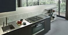 Stainless bench / Integrated cooktop / Integrated sink / Dark timber / Strip splashback