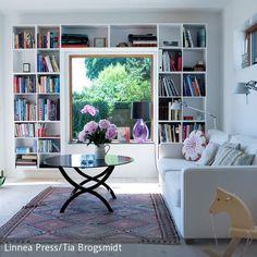 Ein kleines Lesezimmer wurde aus diesem Wohnzimmer geschaffen. Das hängende Modulregal mit den Büchern rahmt das Fenster ein und die weiße Couch hat…