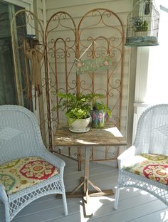 Rusty scrolled iron work and white wicker on the porch. Chateau Chic: Welcome to the Back Porch