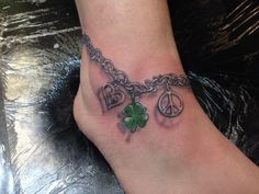 ankle bracelet tattoo with peace sign, clover, double heart charms