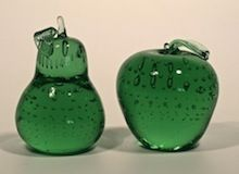 Tabletop accent pieces including green, clear, gold-hued apple and pear-shaped paperweights