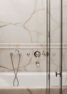 Marble veining bathroom slab on walls with polished nickel faucets hardware
