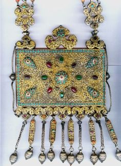 "Another wonderful example of the Uzbeki pieces Linda Pastorino has handled or still owns. Published, with many other great pieces, on her page on the website ""ethnic jewels"". The box functions as a Koran holder, and thus as an amulet, while at the same time it acts as a pendant for a necklace. It is attached to its original strap made of gilt silver, small inset turquoises, and glass and coral stones. It has an opening on the side for prayer placement. It dates back to the 19th c."