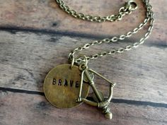 """This necklace was inspired by Disney's Brave. It comes with a 1"""" bronze disc with Brave hand stamped, a large bronze bow and arrow charm that is 3.5cm long, and an optional orange crystal. I can also handstamp any other word you'd like up to 8 letters. This necklace comes with a bronze link chain that is 20"""" long"""