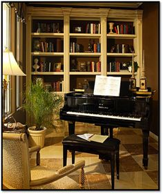 perfect piano and shelves, floor lamp, fern, and waiting arm chair.