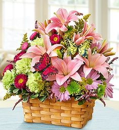 Garden Inspiration- lilies, daisy poms, asters, carnations, poms, heather, solidago and variegated pittosporum in a splitwood handled basket you can later reuse to hold mementos or as a décor item includes a pair of charming butterfly picks $39.99- $59.99