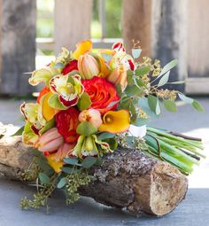 Bouquet in Crisp colors with yellows, reds, and green. Seeded eucalyptus, roses, orchids, and tulips. Summer Time Bouquet Beauty!