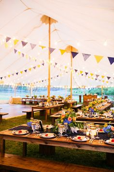 Rustic farm tables and colorful decor at a tented outdoor reception - we love their #Oktoberfest theme! {Mark Davidson Photographer}