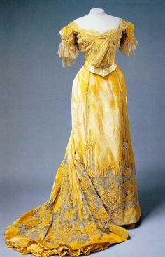 1900s Alexandra Feodorovna's yellow evening dress. The bodice puffing of the early 1900s is handled creatively with a diagonal panel of folded material blending with the folded material of the neckline. The waist band is a definite point of attention.