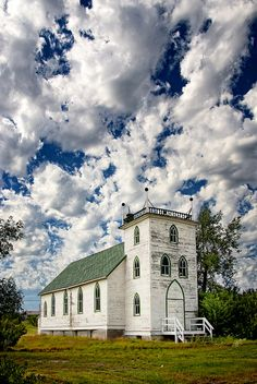 The billowing clouds , with a bit of dark blue sky peeking thru, makes this an awesome picture of a little country church~❥