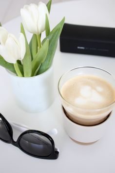 I love me some Coffee and flowers...aaaand sunglasses on a white tabllle