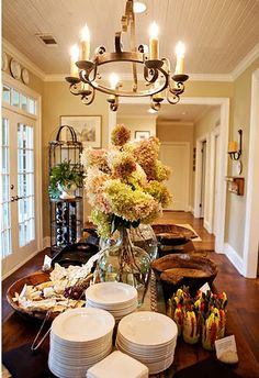 Buffet table/ love the huge glass bottle with flowers in in, stands out and could even put a goldfish in it along with big flowers!  Or is that tacky???