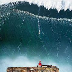 A Perfect Storm hits Nazaré, Portugal  ... not only that but the surfing record was recorded here .. you can see Garrett Mc Namara on his board riding down the face of the huge wave !!!!!!!!!!!!