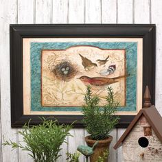 This canvas-look print, framed in black, features birds, a nest with eggs, and a feather with a cream and blue border.