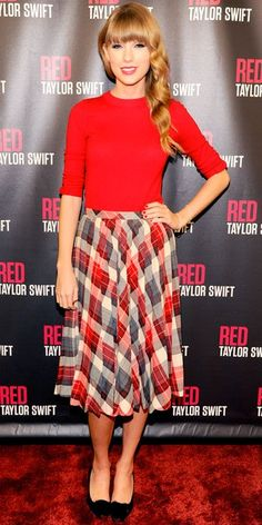 Taylor Swift in a red blouse with a plaid tea-length skirt & flats