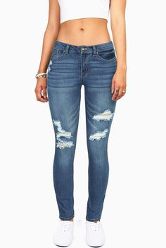 Mid-rise skinny jeans with light distressing and rips across the front. Traditional 5-pocketc construction with button and zip fly closure. Perfect casual pair of jeans to wear with anything. True den