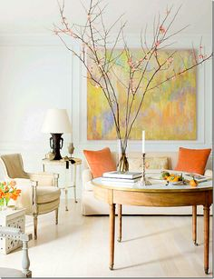 Just beautiful!  I love the pops of orange that come from the painting.  Instead of a coffee a center table – on wheels is used  for easy movement.