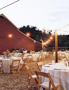 Outdoor barn reception--hay on the ground, burlap table clothes, nice wooden folding chairs, and lights strung overhead.