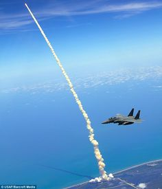 Launch of the Space Shuttle Atlantis while a F15 Strike Eagle is patrolling the skies. Photographer: Cpt. Zachary Bartoe.