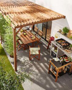 Une cuisine extérieure sous une pergola en bois