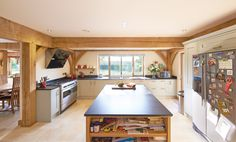 Large central kitchen island with underneath storage, wide cooker and glossy glass hob hood above, light grey cabinets and a dark surface top, large oak posts and beams.