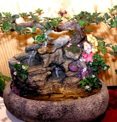 """Item Number: CD27 Bowl Style: Oval Lotus Bowl Color: Textured Grey Stone Bowl Size: 14in. X 17in. diameter Approx. Height: 15"""" to 17"""" (from bottom of bowl to top of tree) An oval lotus fountain that is both magical and whimsical.Acolorful fairy sits among a silk ficus tree and flowering shrubs. Find treasures of clear"""