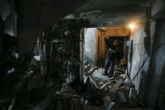 A man shows a staircase at a multi-storey block of flats damaged by shelling in Yenakieve town, northeast from Donetsk, February 2, 2015. REUTERS/Maxim Shemetov