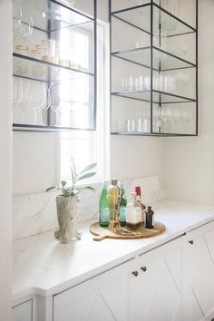 In this beautiful butler pantry, white walls frame two mounted iron and glass shelving units hung flanking a small window as a honed white marble countertop sits atop white cabinets finished with a diamond overlay and antiqued brass knobs.