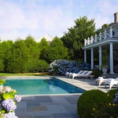 Hydrangeas soften the hardscaping of the pool area, embellishing the classical theme. - Traditional Home ® / Photo: Tria Giovan
