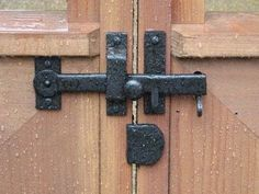 Cast Iron Gate Kit with Drop Bar, Thumb Latch, & Gate Stop - On a wooden rainy gate
