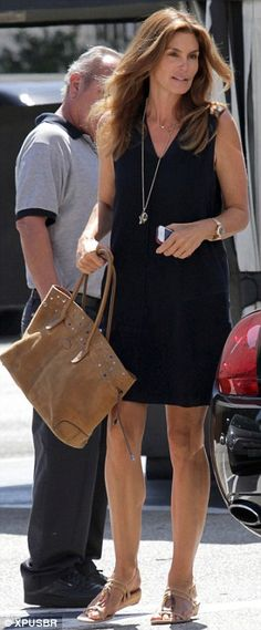 Ageless: The brunette beauty showed off her sculpted figure in a sleeveless navy dress