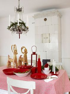 red gingham tablecloth, white tiled Swedish stove and a chandelier with greenery - classic Scandinavian!