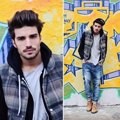 A more focal view of a man, surrounded by bright colors in an outfit with more toned down colors, but the graffiti art around him portrays colorful hues that brighten the image.  Mens Urban Fashion