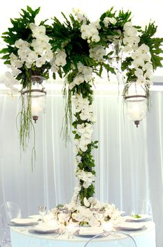 A lush floral centerpiece showcases crisp white phalaenopsis orchids and two hanging lanterns illuminated by candles.