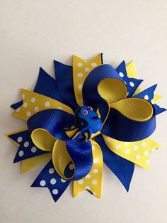 Dorys Hair Bow. This hair bow is layered with lots of ribbon in blues and yellows. Measures approximately 5 across and comes an alligator clip.