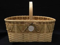 """Burlap market revised basketweaving kit This version of our Williamsburg Market Basket is woven for that authentic """"Old Time"""" look for a trip to the market in the village of Williamsburg. It features natural and smoked reed and a burlap covered 2"""" maple strip. It is adorned with a hand-made clay woven heart embellishment. Size: 20"""" x 11"""". Basket is 8"""" high and handle is 14"""" high. $59.65 for pattern and kit"""